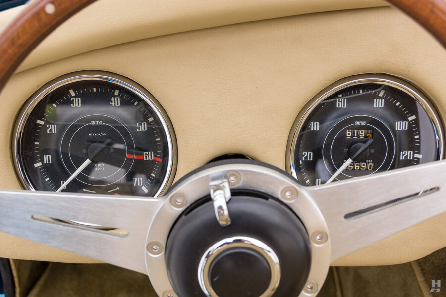 Close Up of Speedometers and Steering Wheel of Classic 1957 Daimler SP250 Car at Hyman Dealership in St. Louis, Missouri